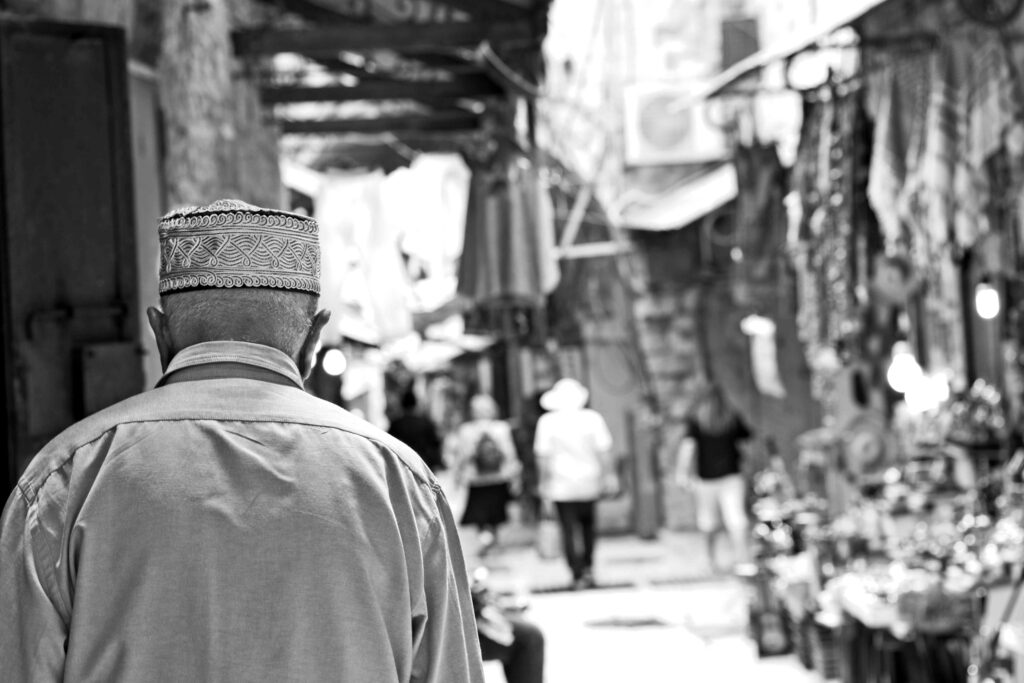 An old Palestinian watching the tourists looking at the goods offered by the local shop owners